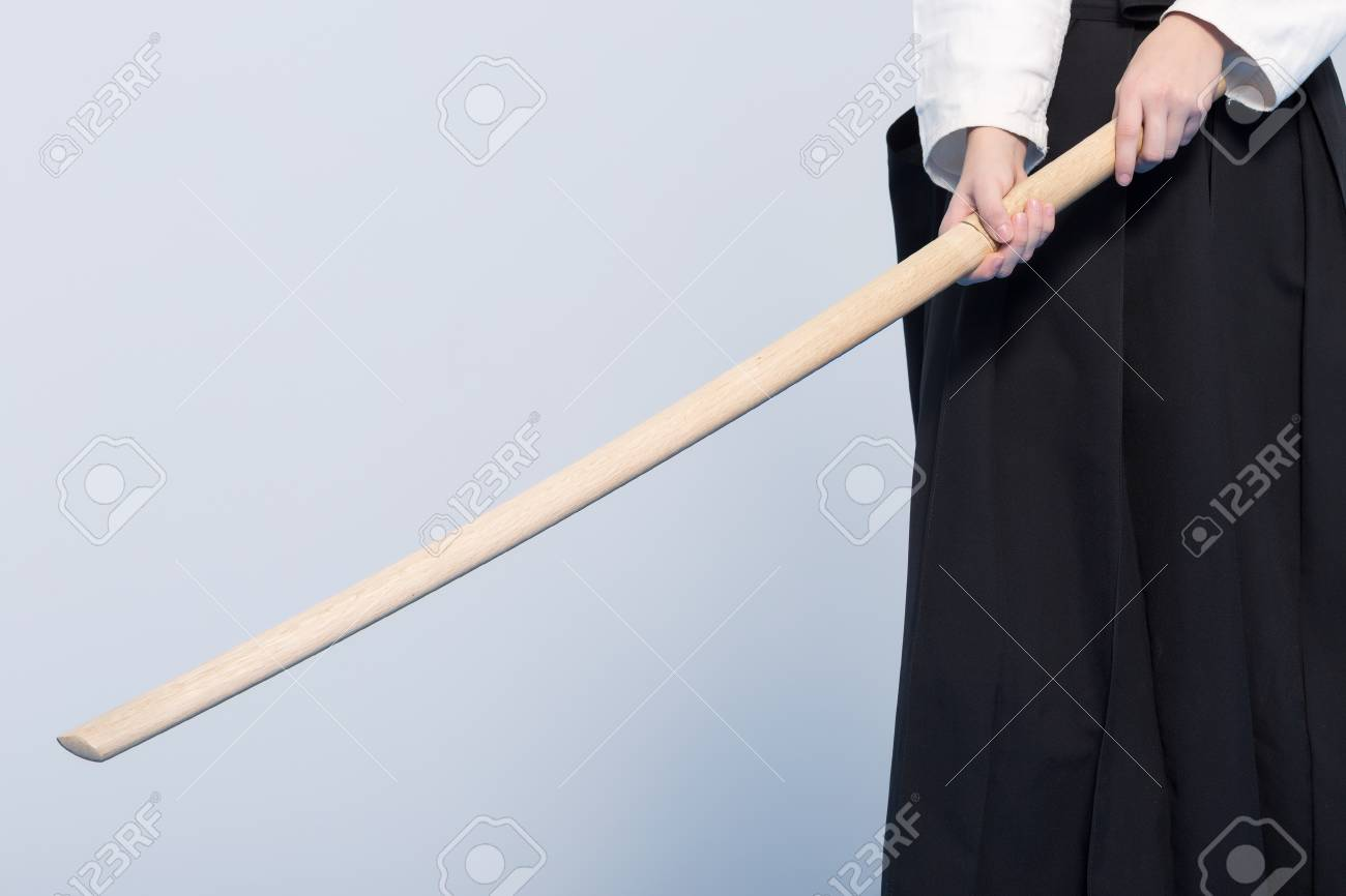 A person in black hakama standing in fighting pose with wooden sword bokken - 93377617