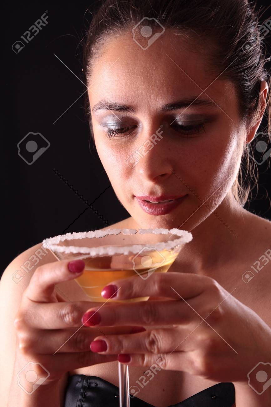 Beautiful young woman holding a martini glass Stock Photo - 3413024
