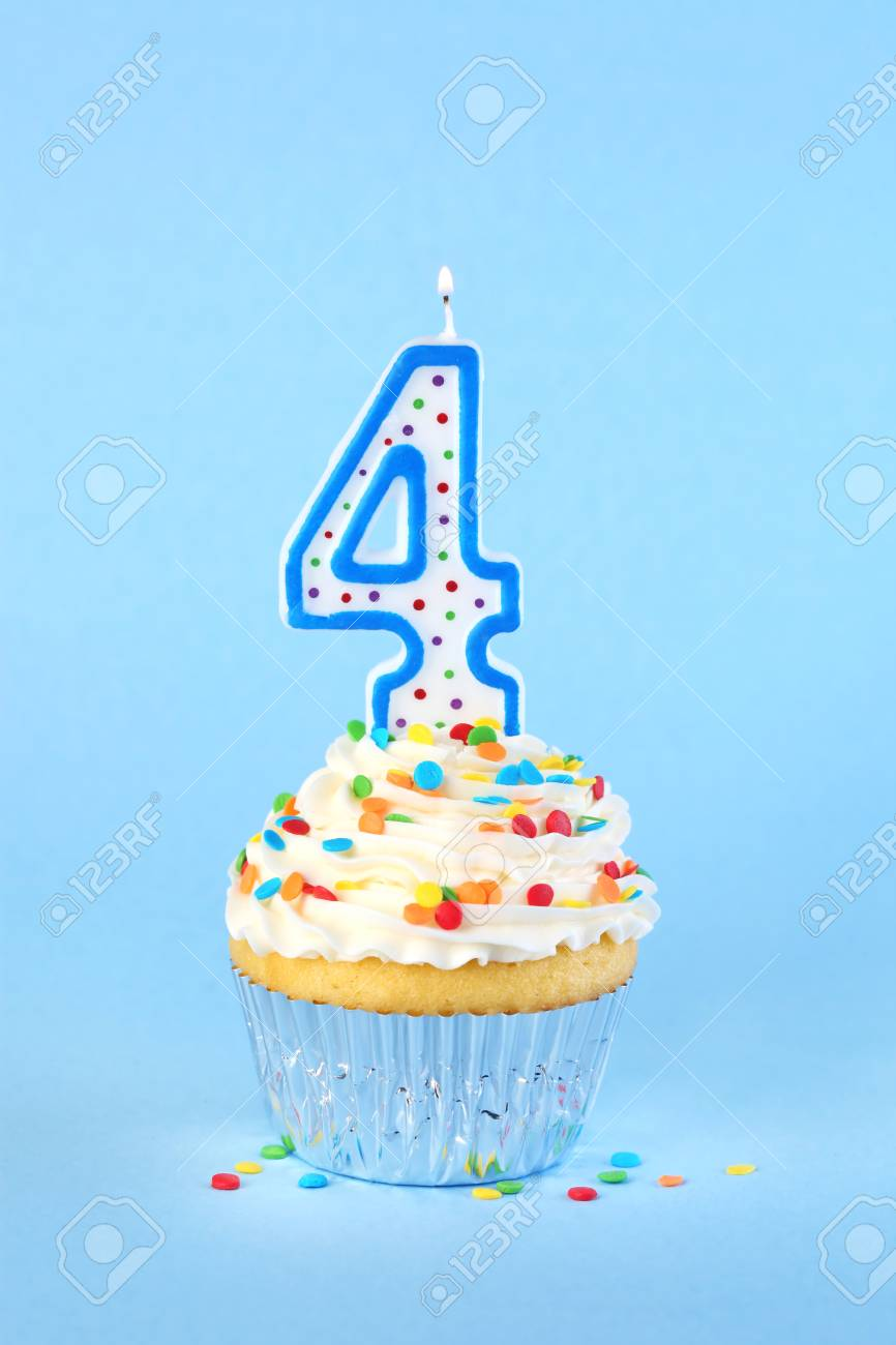 Iced Birthday Cupcake With Lit Number 4 Candle And Sprinkles Stock Photo