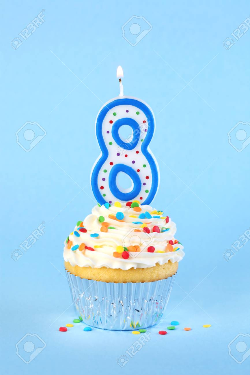 Iced Birthday Cupcake With Lit Number 8 Candle And Sprinkles Stock Photo