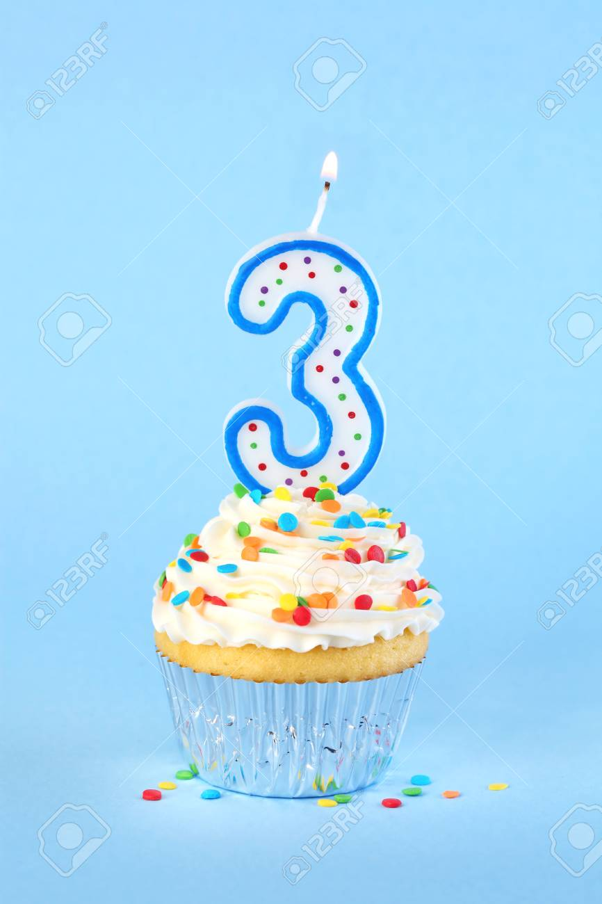 Iced Birthday Cupcake With Lit Number 3 Candle And Sprinkles Stock Photo