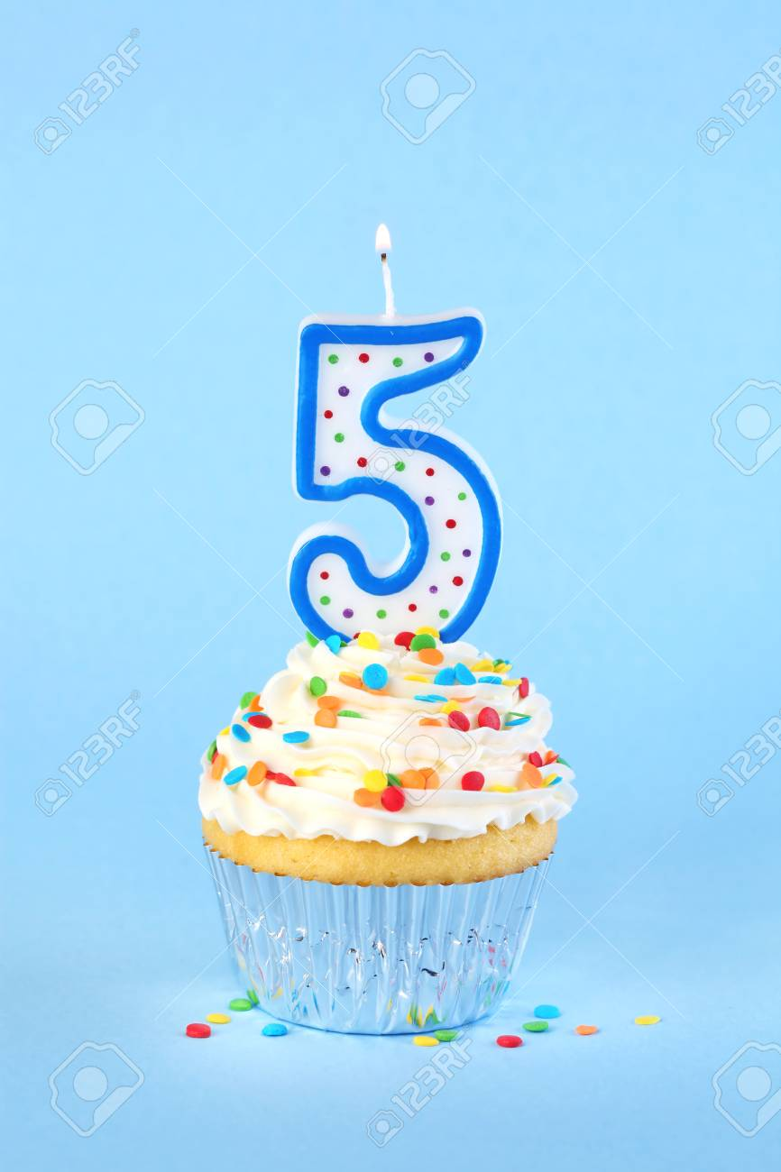 Iced Birthday Cupcake With Lit Number 5 Candle And Sprinkles Stock Photo