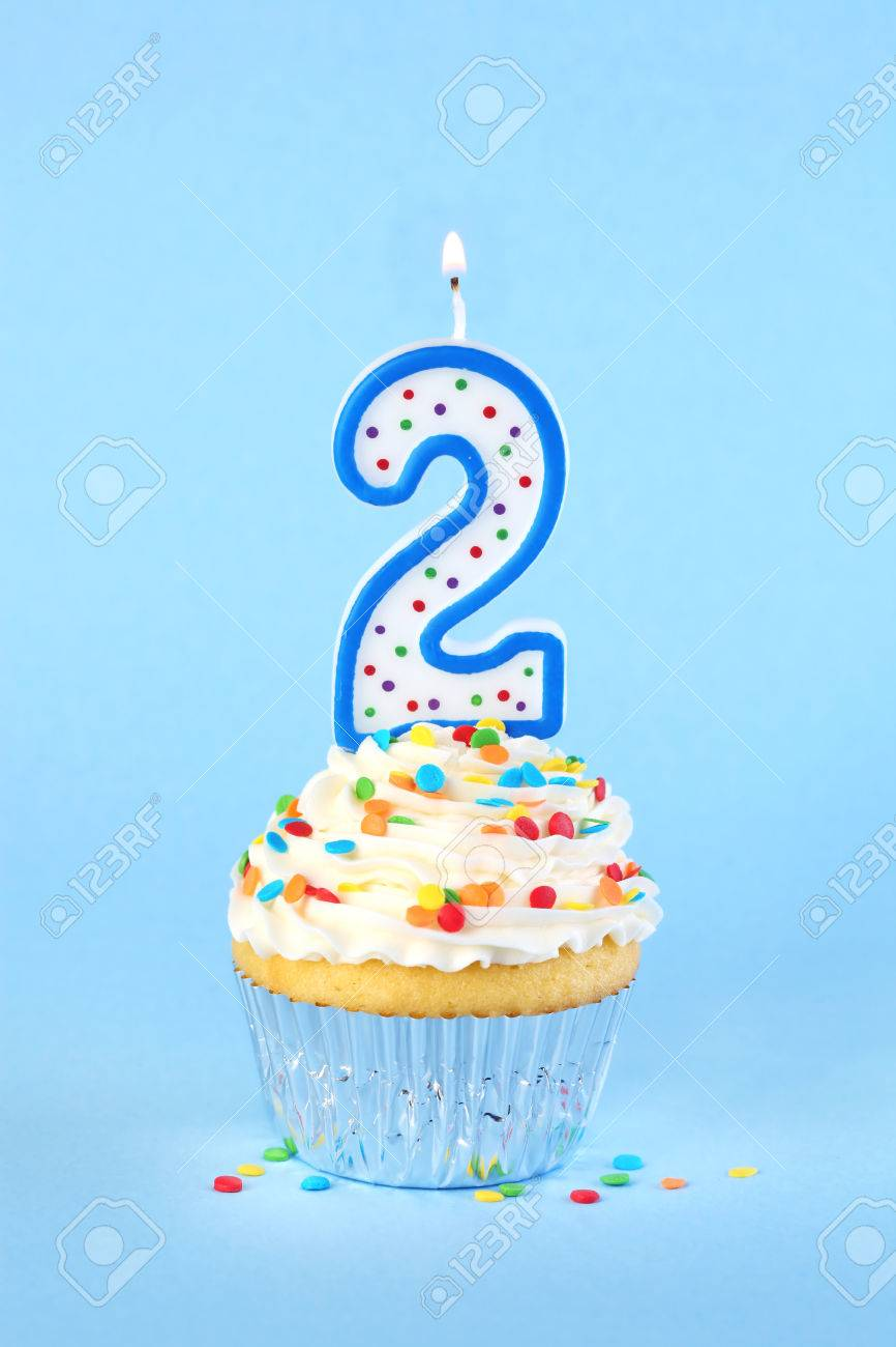 Iced Birthday Cupcake With Lit Number 2 Candle And Sprinkles Stock Photo