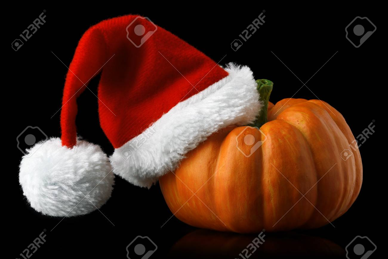e8f4af01435 Single orange pumpkin with Christmas Santa hat isolated on black Stock  Photo - 108942349