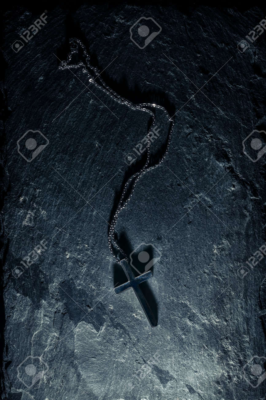 Christian cross necklace on slate background with the crucifix casting a dark shadow. - 158384538