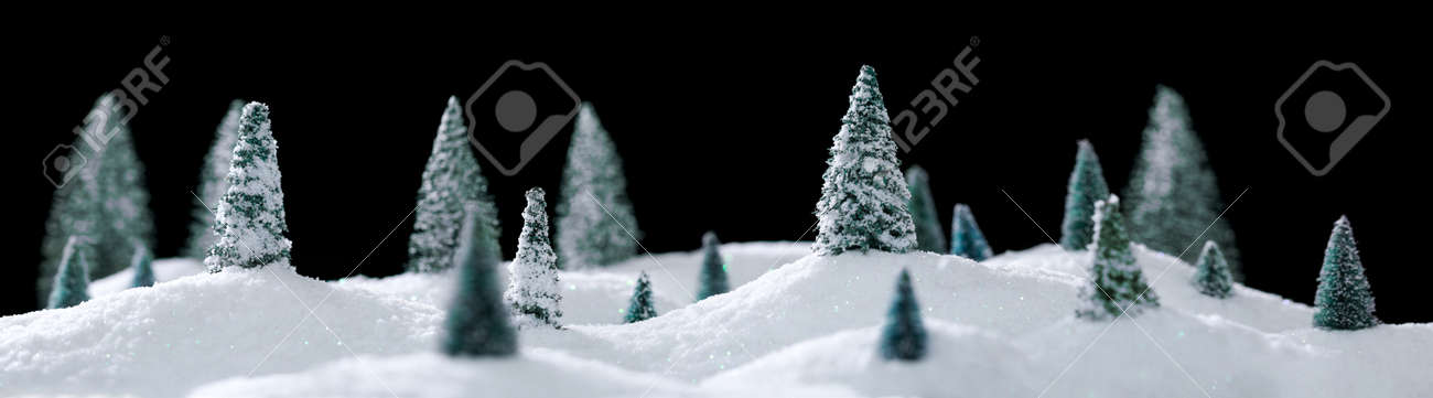 Wintry forest scene of miniature snow covered trees on glittering snow drifts isolated on black - 158384542
