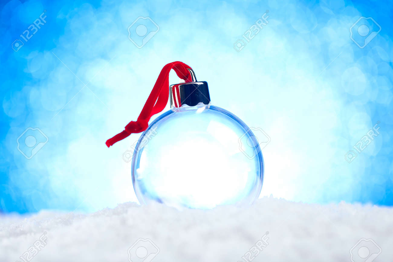 Clear empty Christmas ornament with red ribbon sitting in snow with shiny blue lights bokeh background - 158384541