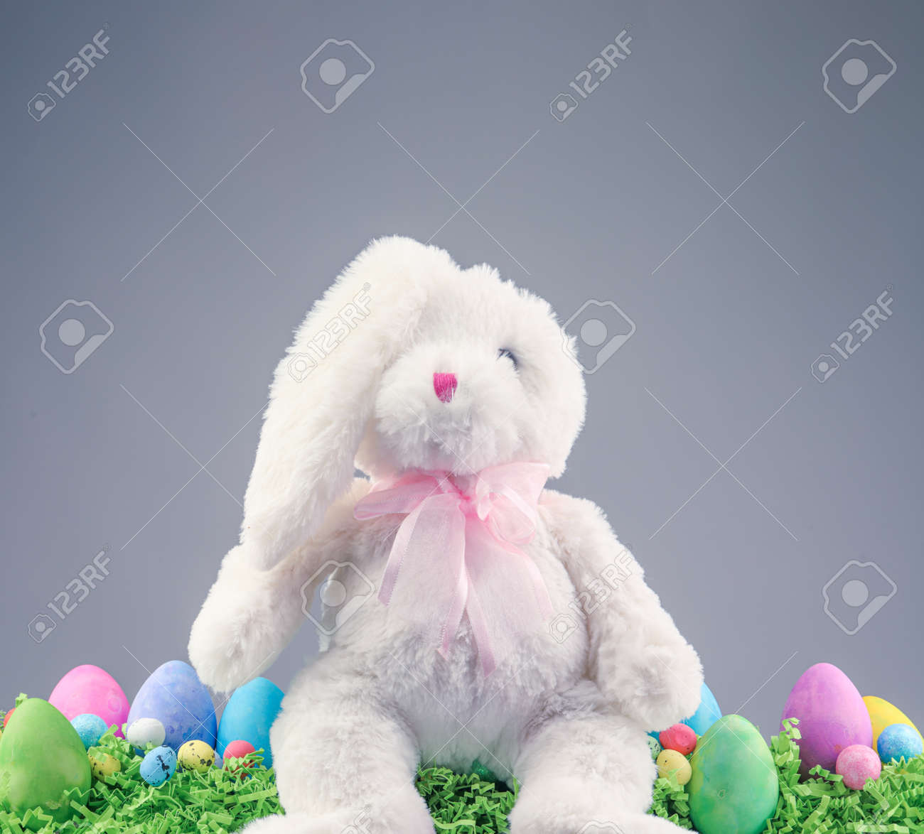 Stuffed animal Easter Bunny surrounded with painted Easter eggs and colorful decorations. - 165169623