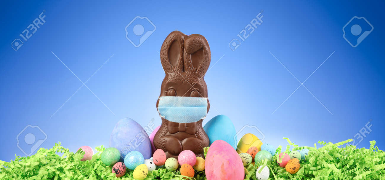 Chocolate Easter bunny wearing a medical mask surrounded by painted Easter eggs and colorful decorations. - 165607657