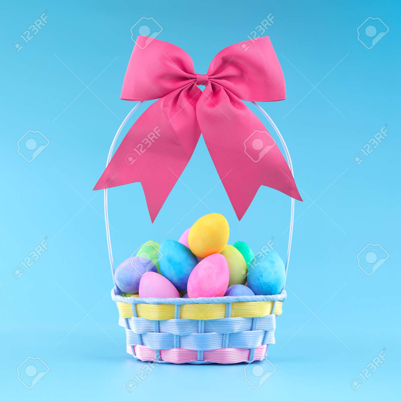 Easter basket for Easter egg hunt filled with colorful painted Easter eggs, topped with a pink bow. - 166138549