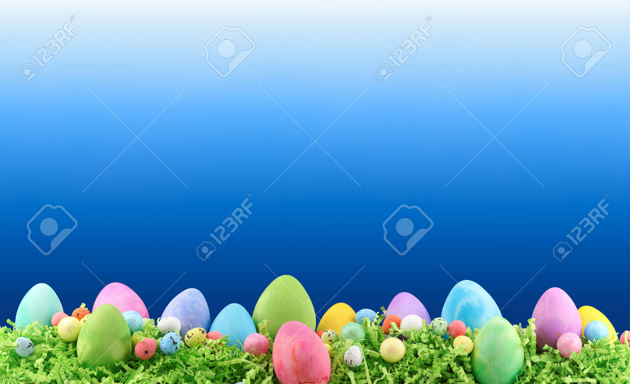 Painted Easter eggs and decorations on arranged on Easter grass with blank copyspace for text. - 166138552