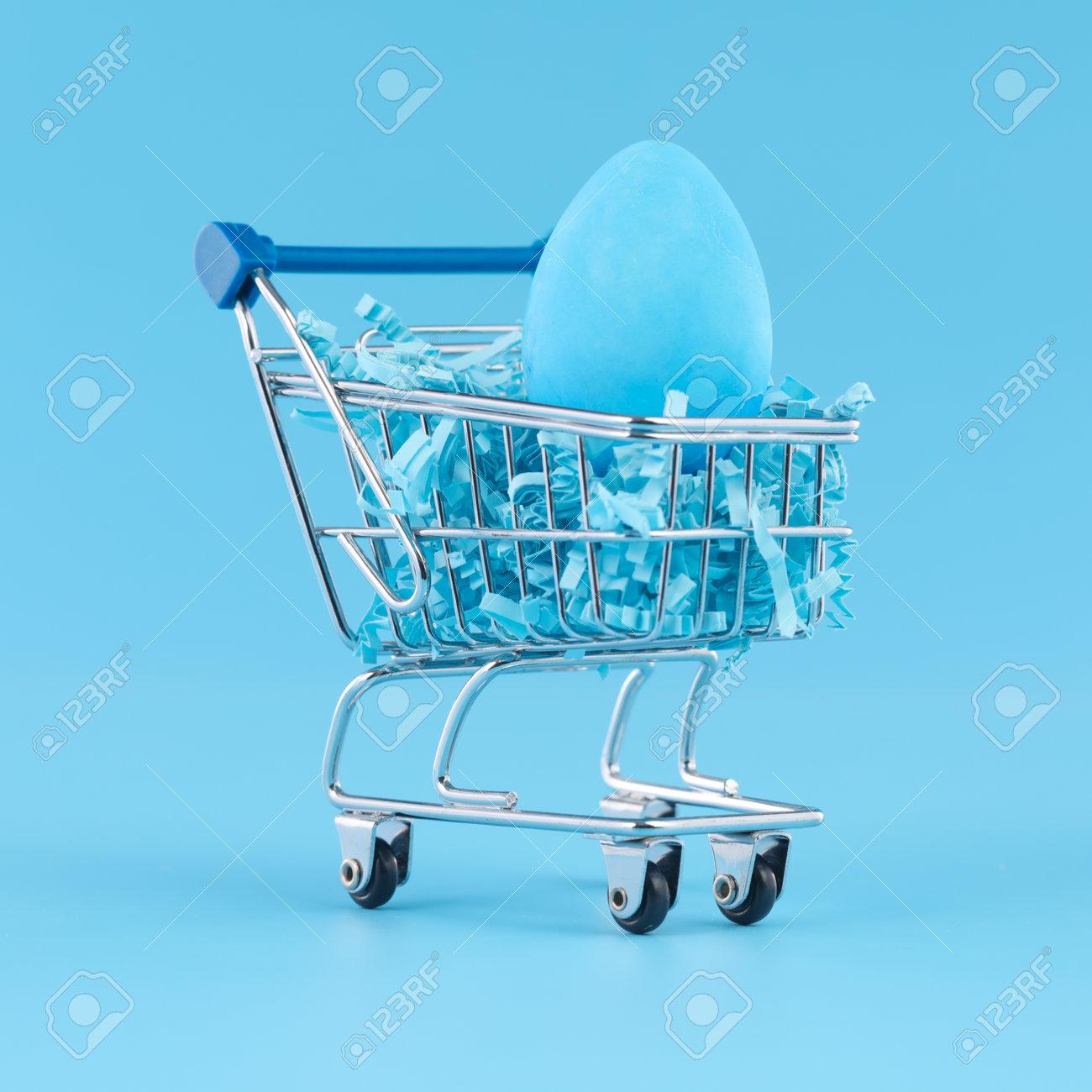 Blue Easter egg in shopping cart for Easter shopping concept. - 166132232