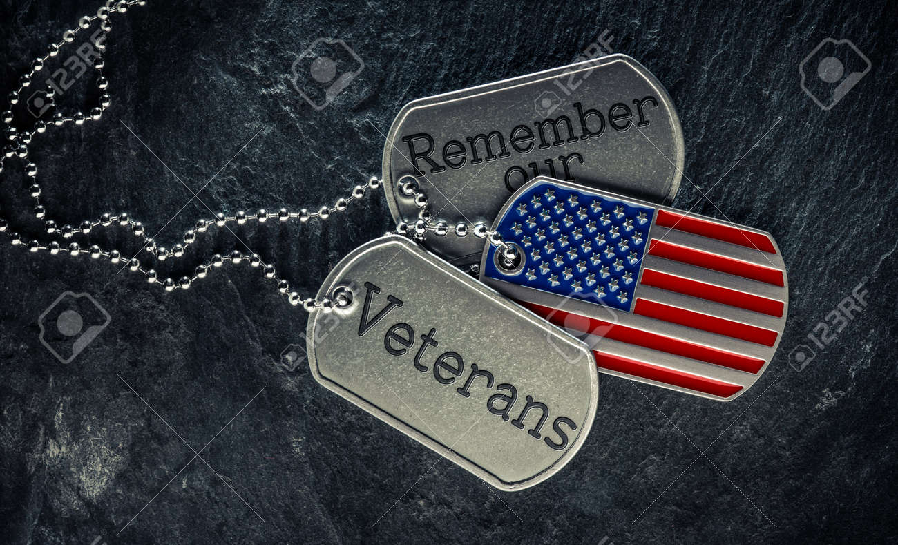 US military soldier's dog tags engraved with Remember our Veteran's text and in the shape of the American flag. Memorial Day or Veterans Day concept. - 169060086