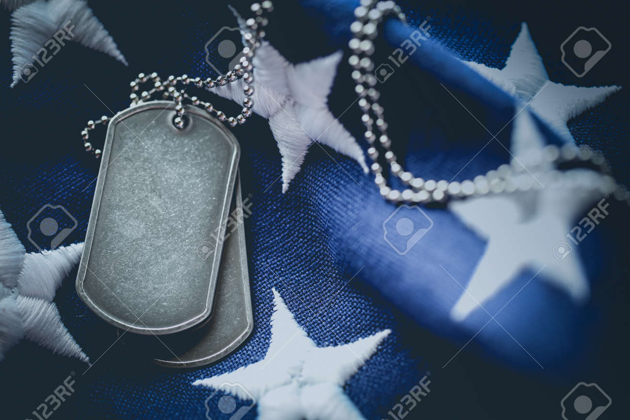 Worn USA military dog tags close up on US American flag with blank space for text - 169060097