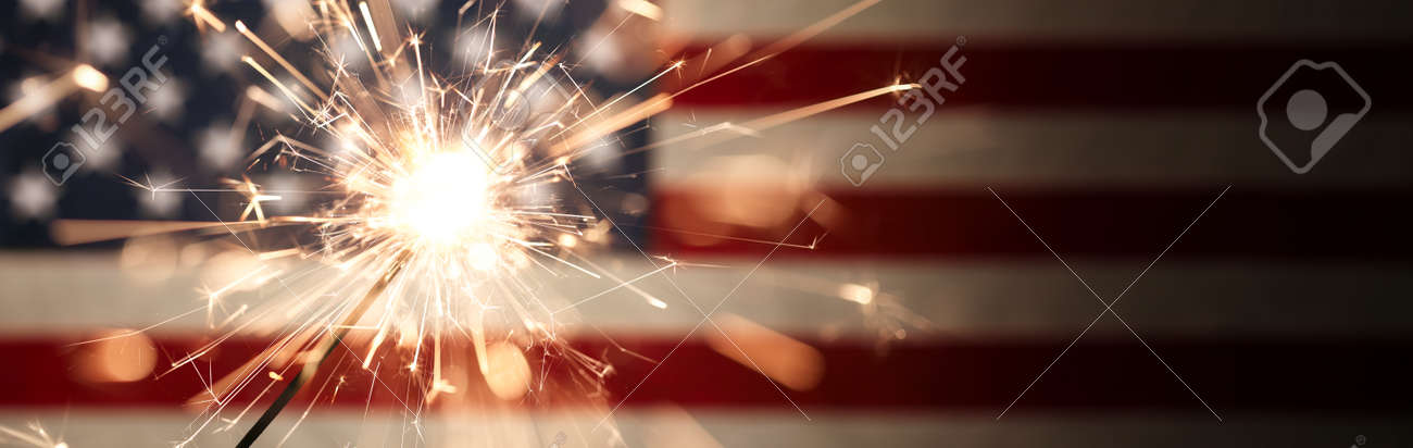 Sparks flying off a burning sparkler in front of the US American flag for patriotic 4th of July celebration. - 170507374