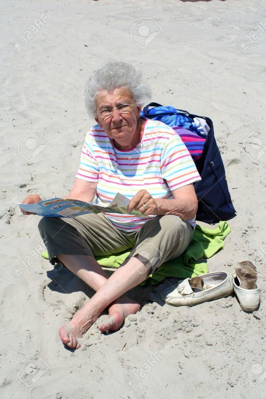 Senior citizen woman sitting on a beach reading a brochure. Stock Photo - 11377912