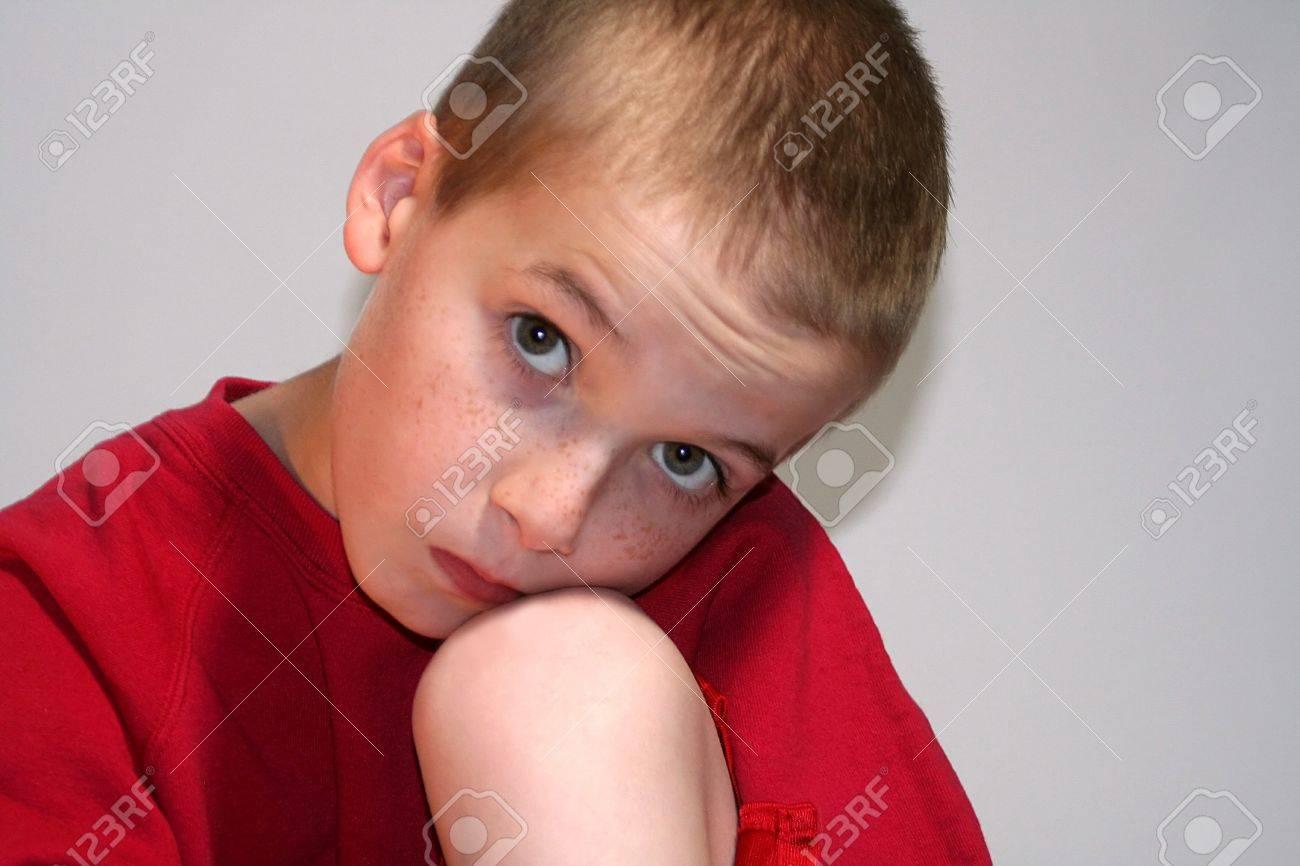 Sad Boy Closeup Against Knee Looking Up Stock Photo - 16882687