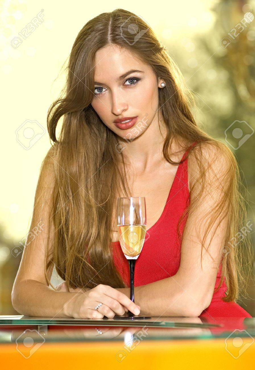 beautiful pretty woman in red dress on a sofa with glass of champagne Stock Photo - 5967331