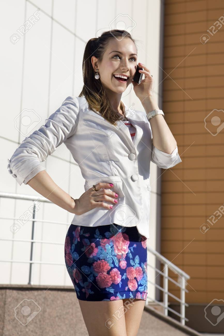 happy young girl speaks by a mobile phone in the street Stock Photo - 6961463