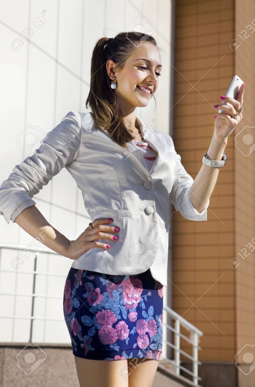 happy young woman holds mobile phone, she is near a building Stock Photo - 6995803