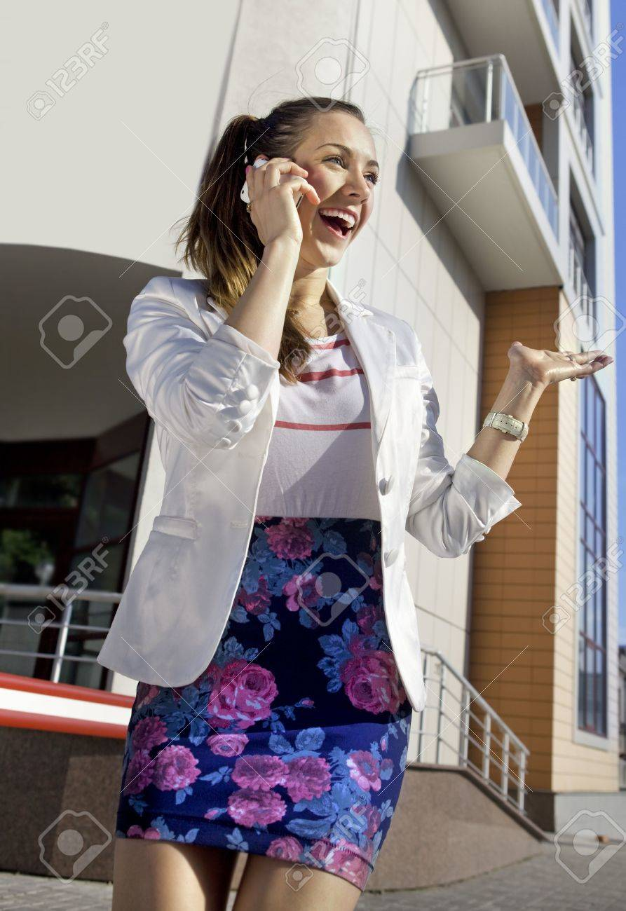 happy young girl speaks by a mobile phone in the street Stock Photo - 7063384