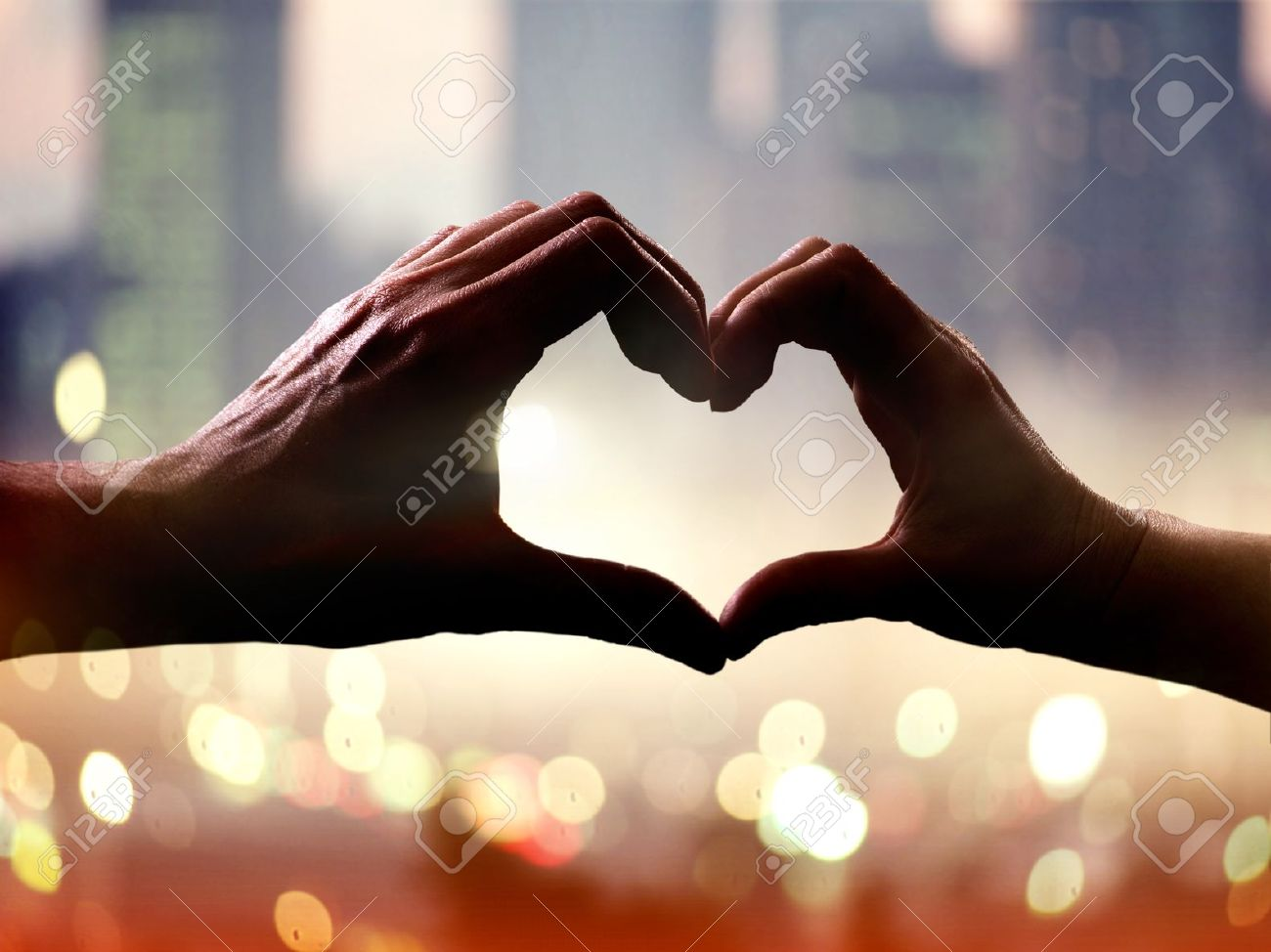 Silhouette of hands in form of heart when sweethearts have touched Stock Photo - 11885128