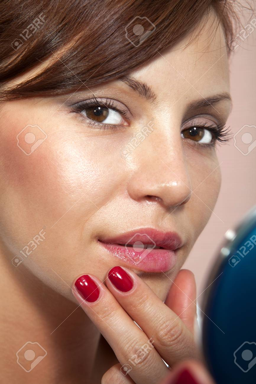beautiful girl smartens up in front of compact mirror Stock Photo - 13603898