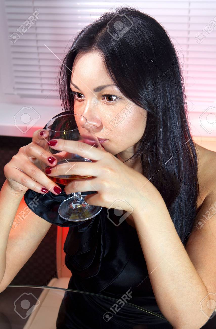 beautiful woman in black dress on sofa with glass of brandy Stock Photo - 16409737