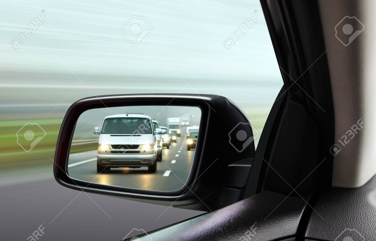reflection of traffic flow in left side rear view mirror at twilight time - 95531456