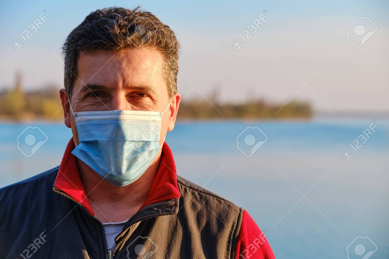 Mature caucasian man wearing protective surgical face mask to prevent coronavirus, on the lake background. Close Up portrait, copy space - 145319062