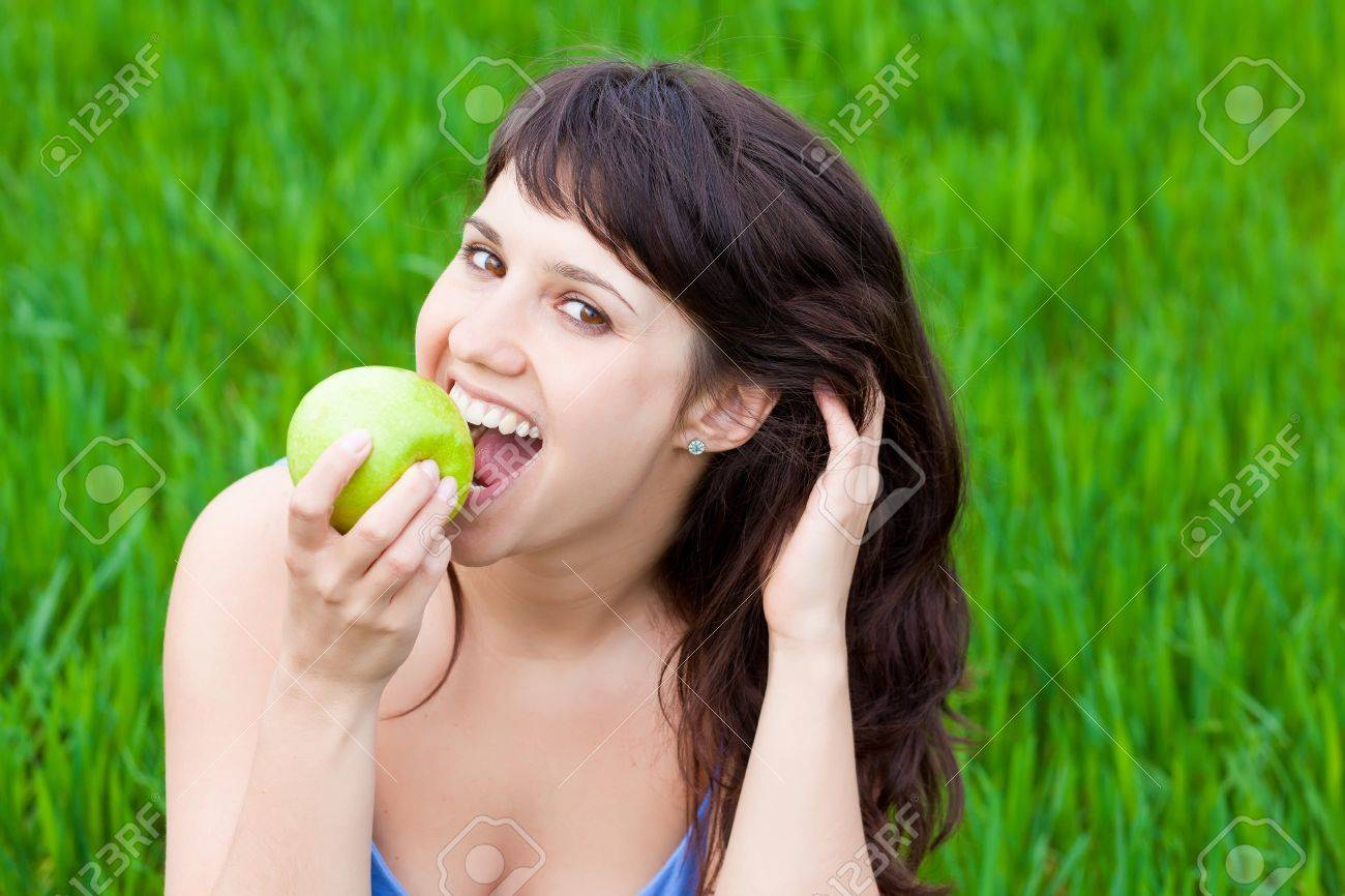 Girl eating a green apple on a grass Stock Photo - 9650314