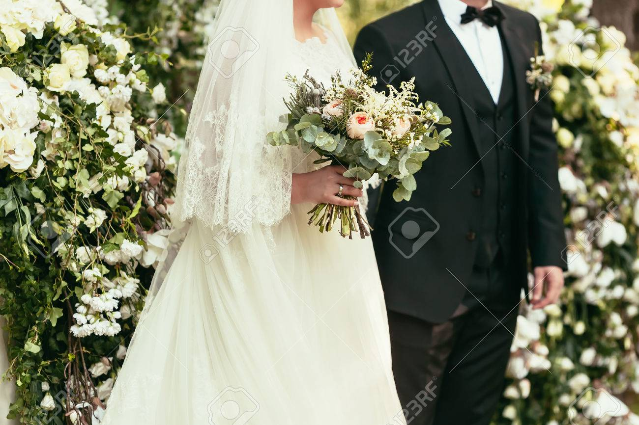 Groom In Black Suit And Bride In White Wedding Dress With Rustic