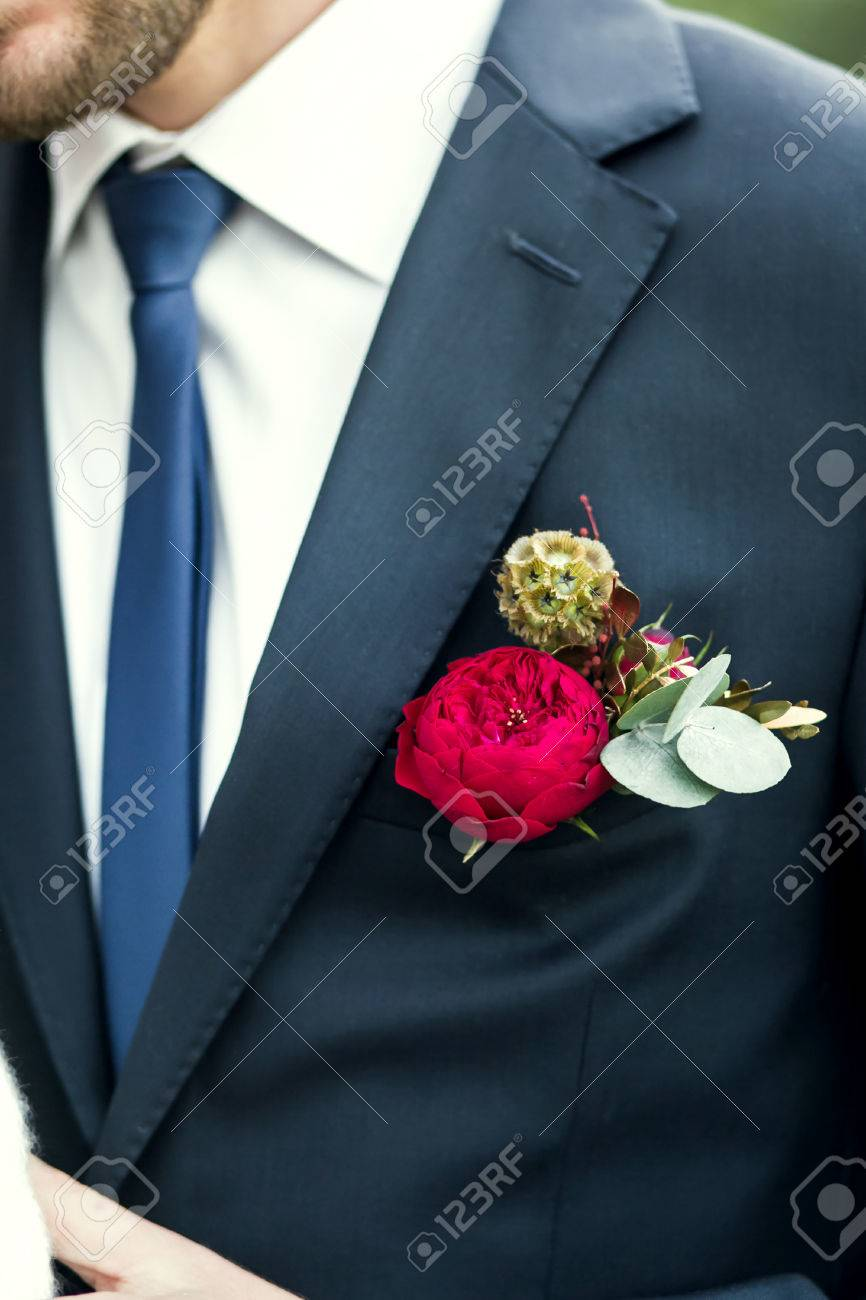31fd6ae13 grooms with blue tie and red rose boutonniere on wedding day Stock Photo -  56598174