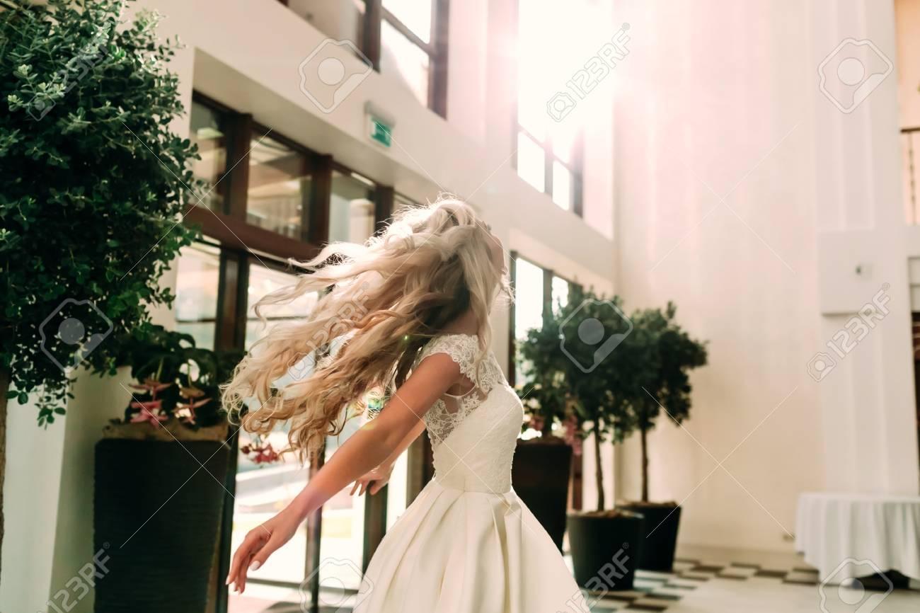 d4cb192751 Hermosa Joven Novia Con Una Sonrisa En Un Vestido Blanco Está Girando  Alrededor De Sí Misma En La Danza. Chica Elegante Feliz Agitando El Cabello  A La Luz ...