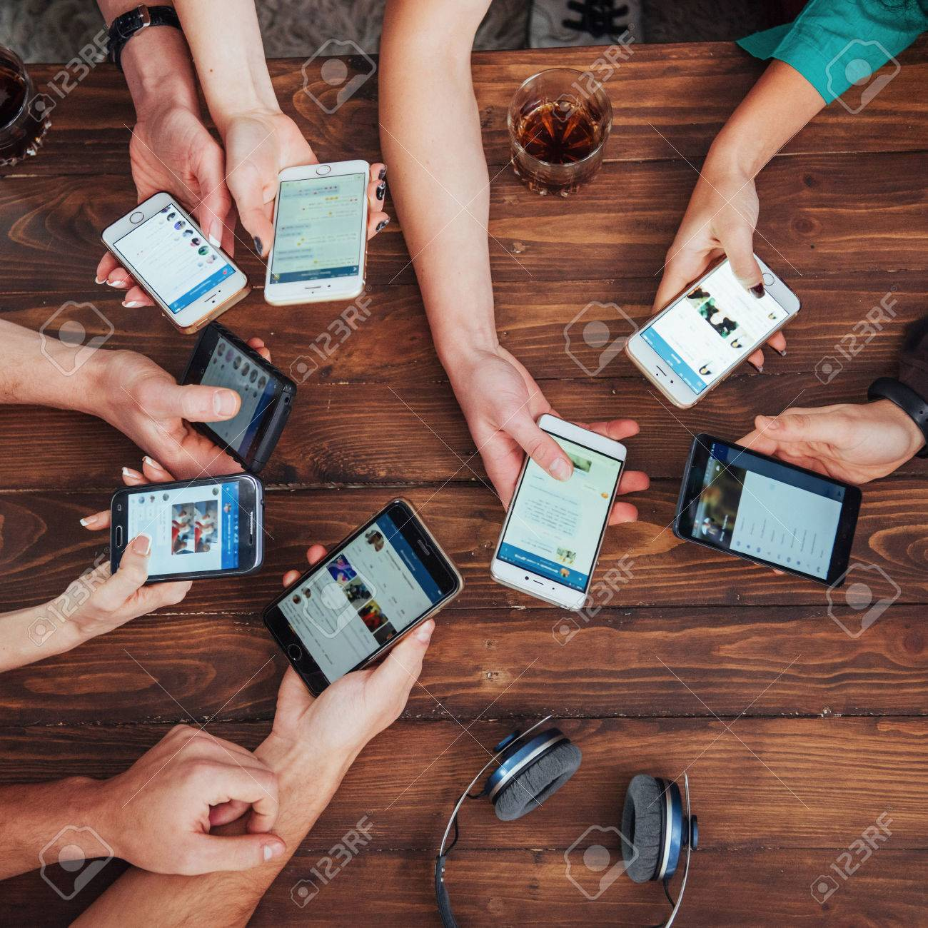 Top view hands circle using phone in cafe - Multiracial friends mobile addicted interior scene from above - Wifi connected people in bar table meeting - Concept of teamwork - 71057263