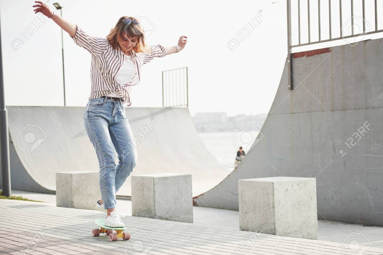 A young sports woman who rides in a park on a skateboard - 134067899