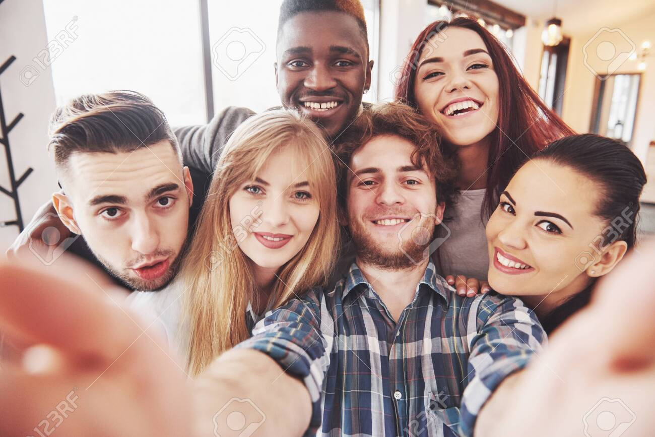 Friends having fun at restaurant. Three boys and three girls making selfie and laughing. On foreground boy holding smart phone. All wear casual clothes. - 134491586