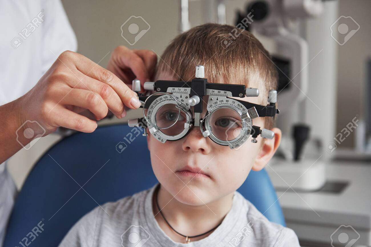 Little boy with phoropter having testing his eyes in the doctors office. - 134545022