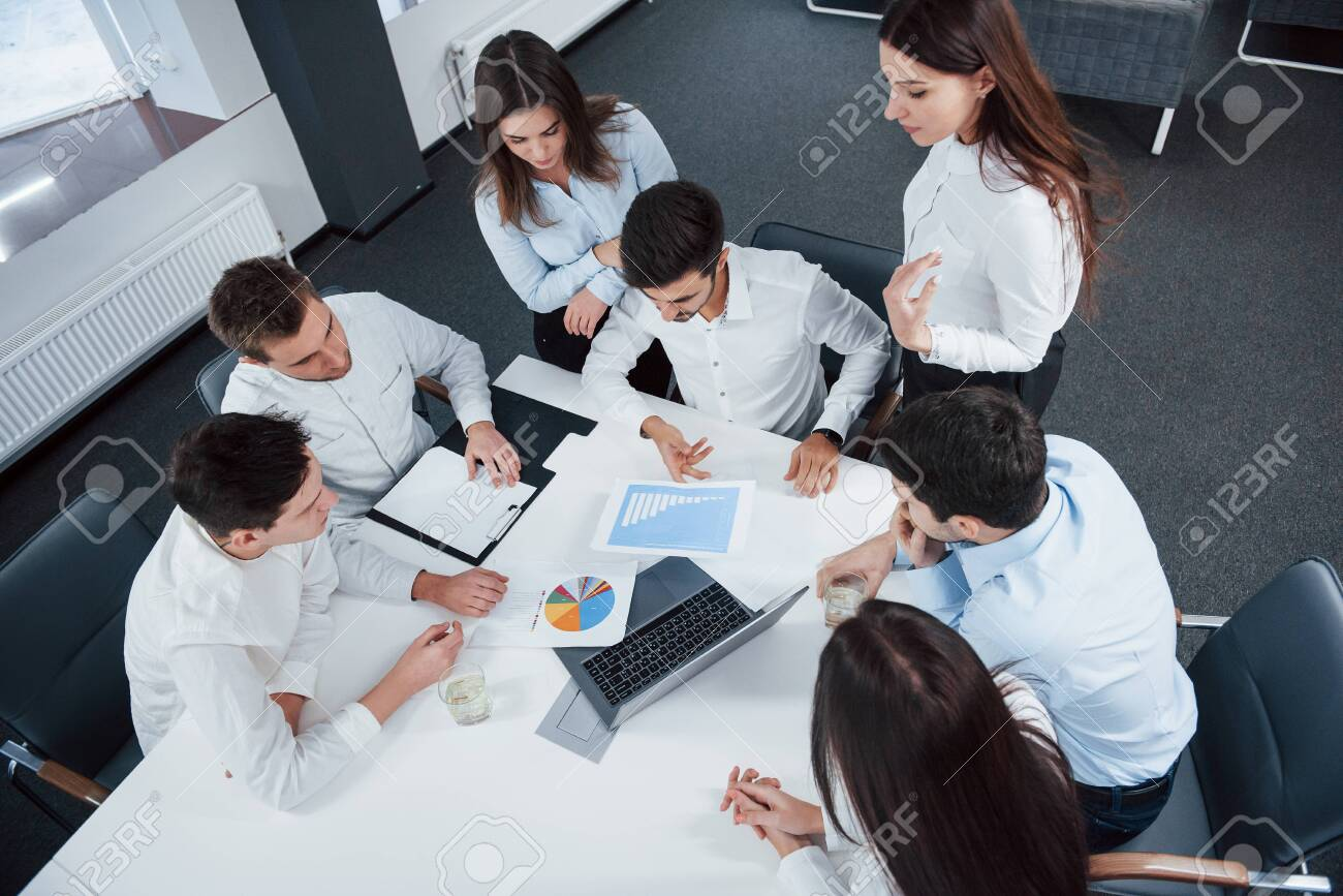 Top view of office workers in classic wear sitting near the table using laptop and documents. - 134794531