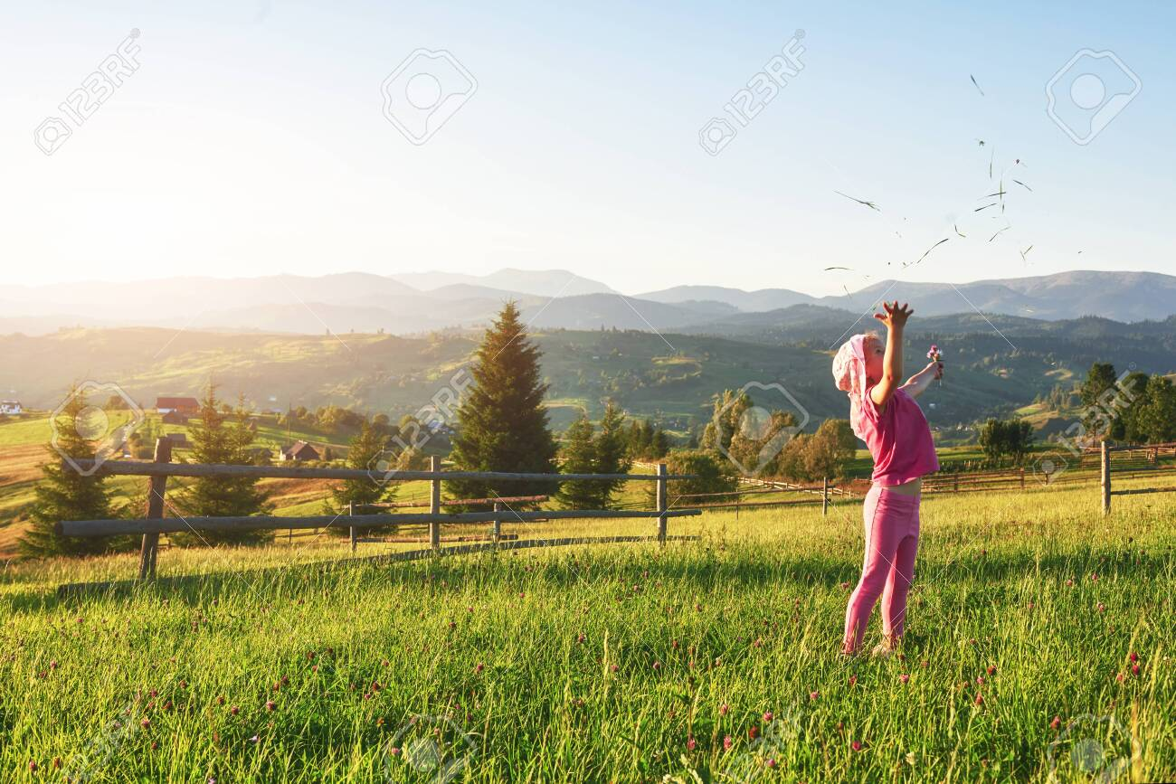 Cute happy little baby girl play outdoors in the early morning in the lawn and admiring mountains view. Copy space for your text. - 135144777