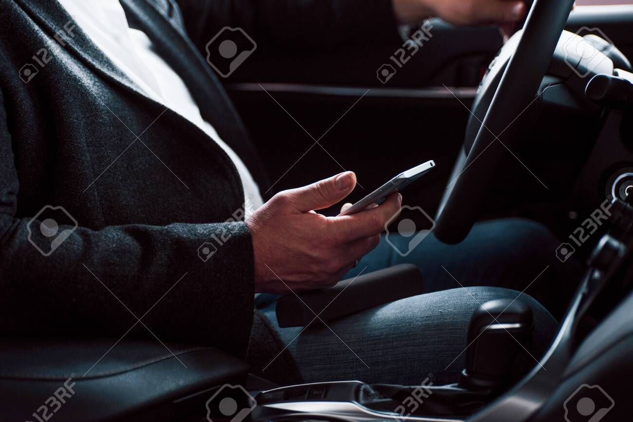 Rich clothes, car and mobile device. Working in the car using silver colored smartphone. Senior businessman. - 134886738