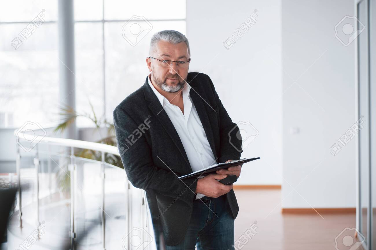 Modern looking place. Photo of senior businessman in the spacious room with plants behind. Holding and reading documents. - 135166269