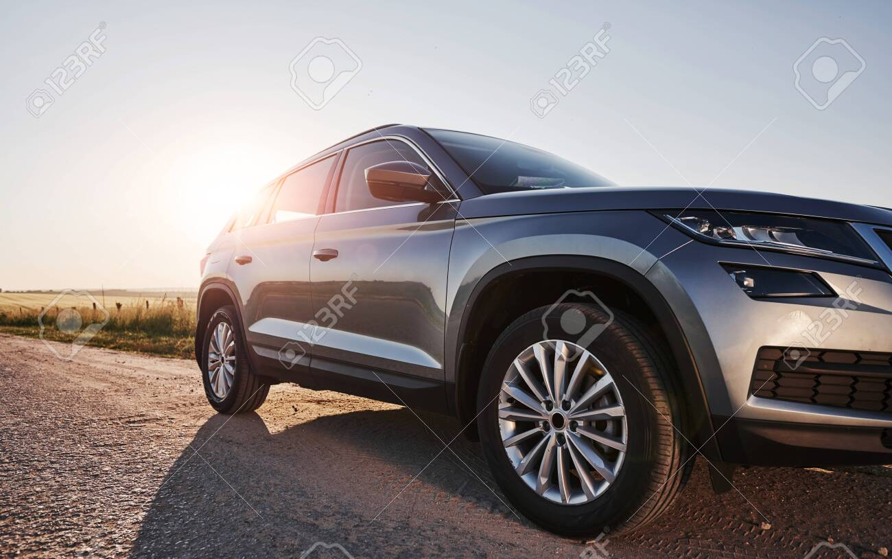 Sunlight goes over automobile. Modern new car parked on the side road at countryside at daytime. - 135507642