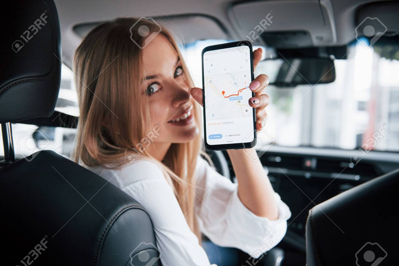 How far can I go. Beautiful blonde girl sitting in the new car with modern black interior. - 135889373