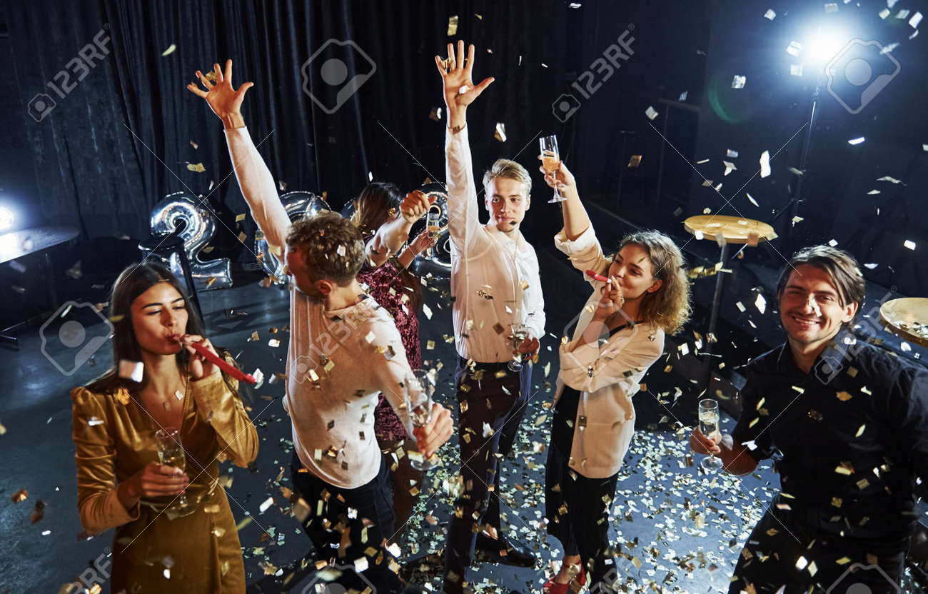 Confetti is in the air. Group of cheerful friends celebrating new year indoors with drinks in hands. - 157225221