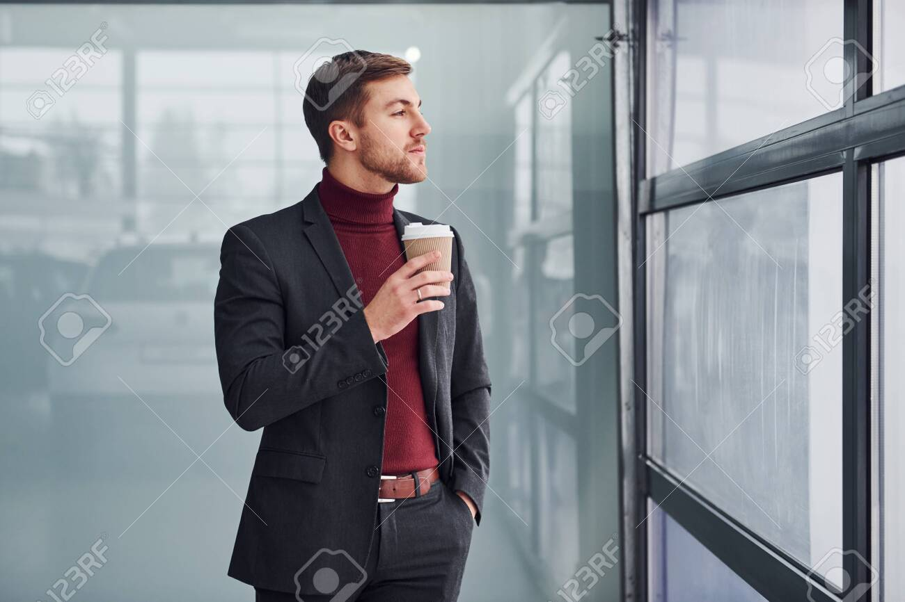 Young business man in luxury suit and formal clothes wth cup of drink is indoors in the office. - 158303064