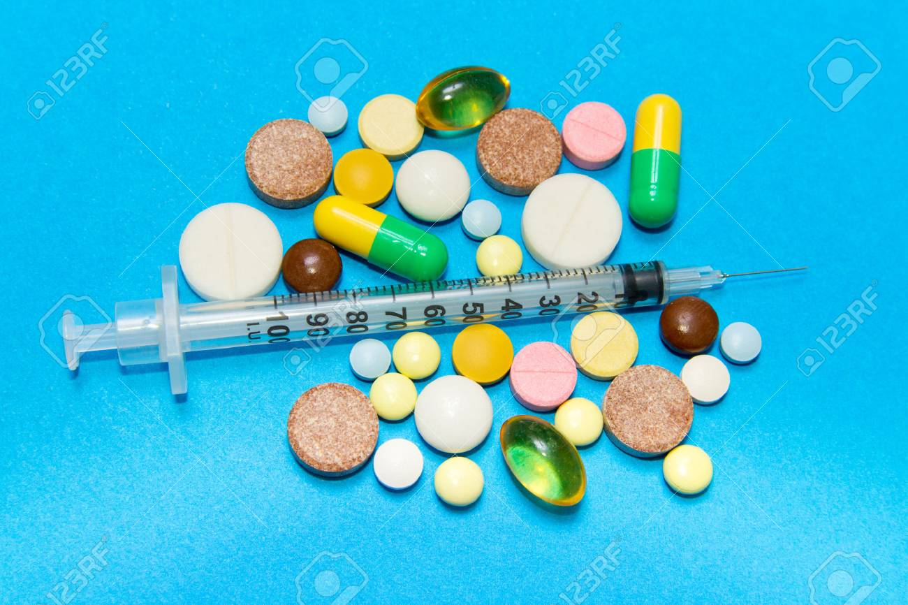 Opioid epidemic .Opioid Pills. Drug abuse Concept - different colored pills and syringe on a blue background. - 92778207