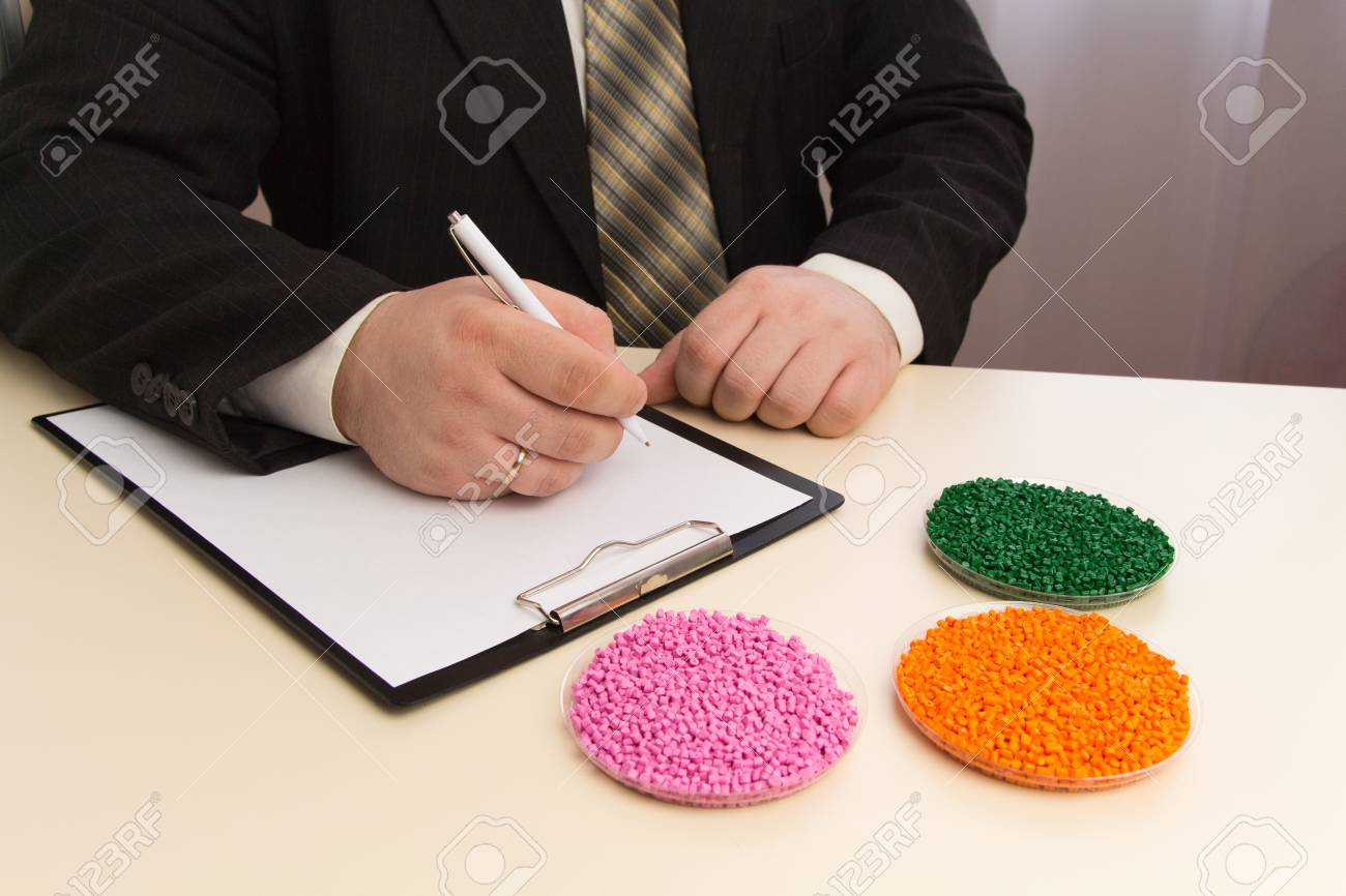 Businessman signs a contract for the supply of plastic granules for industry. Plastic raw material in granules . Polymer, plastic resin. - 97058209
