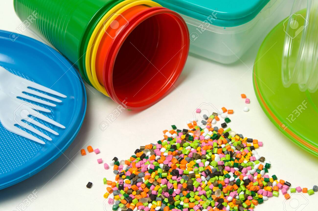 Plastic granules and disposable tableware made of polyethylene, polypropylene polymeric material on a white background. BPA FREE - 150324241