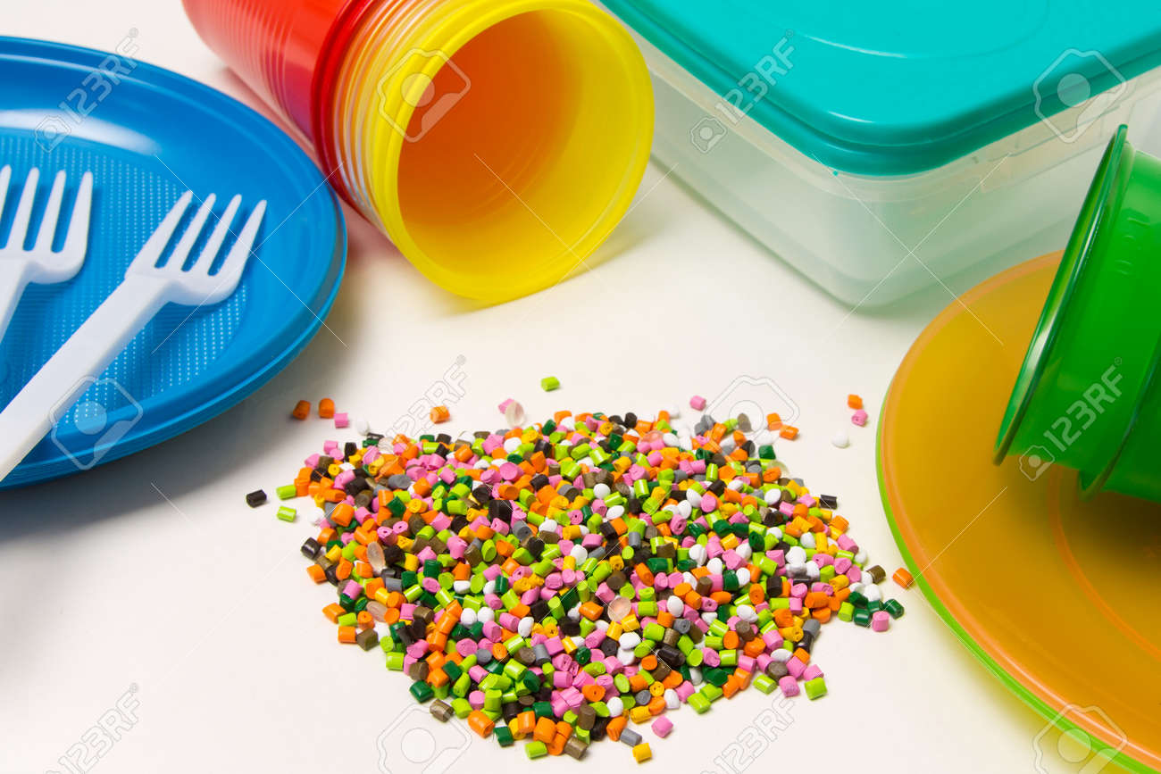 Plastic granules and disposable tableware made of polyethylene, polypropylene polymeric material on a white background. BPA FREE - 150324243
